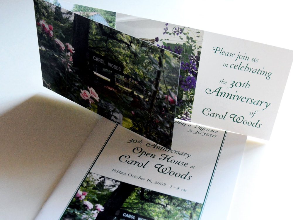 Photograph of a folded, horizontal event invitation with a shorter front piece on top of an open house tour booklet. Both items have outdoor photography of the retirement community's campus and green, curling headline text.