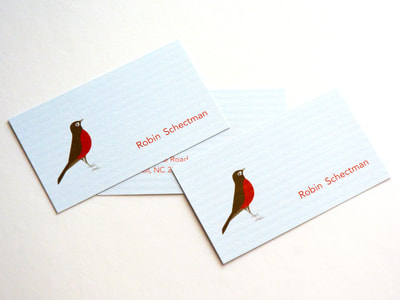 Photograph of the fonts and back of a light blue business card with a horizontal column texture on the paper. A a sweet brown and red-orange robin illustration and red-orange text are printed on it.