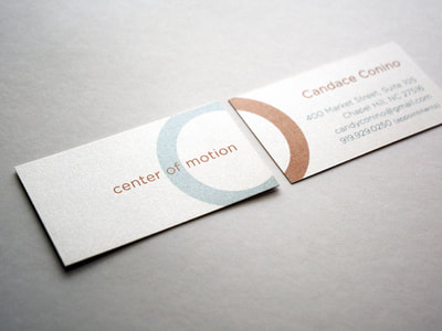 Close-up photograph of business cards with metallic copper and teal ink on a creamy, pearlescent paper. The logo shows the arc of a circle on one side continuing on the other. The font is a sans serif font.