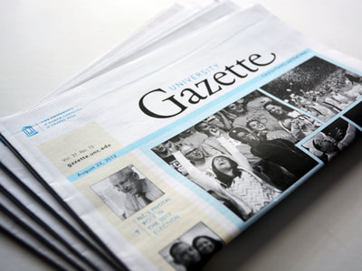 Photograph of a stack of folded University Gazette newspapers. The prominent photo is of a crowd cheering, focused on a girl with her arms up and her face up to the sky. The photography is black and white and the accent colors are light blue and pale yellow.