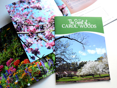"Photograph of several annual reports for Carol Woods: one full cover with ""The Spirit of Carol Woods"" in white against green at the top and a picture of cottages, cherry trees, and a blue sky at the bottom, all with a white swoosh between; a close-up photo of colorful zinnias; and a close-up photo of a redwood blooming next to a plum and white table of contents."