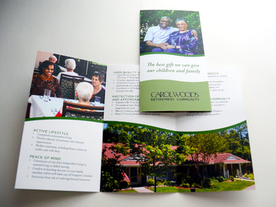 Photograph of a brochure for Carol Woods including photographs of an older African-American couple on the cover and a younger African-American women at a table with older adults inside. A photograph of a Carol Woods cottage with a flowering garden is also inside. Text and accents are black and green.