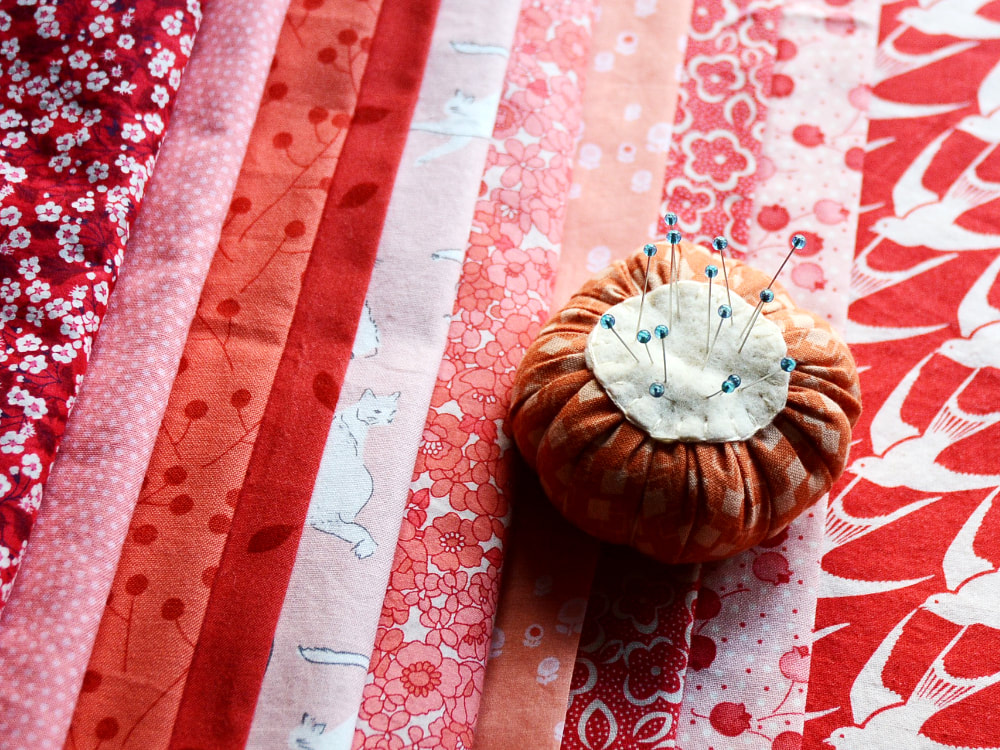 Photograph of a line of folded peach, pink, and red cotton fabrics. Patterns include flowers, dots, leaves, branches, cats, and birds An orange and cream pincushion sits on top and holds pins with blue glass heads.