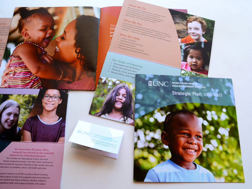 Various printed pieces include a square booklet; a large, vertical brochure; and a folding information card. Orange, purple, red, Carolina blue, and green colors and swooping shapes complement photos of smiling children.